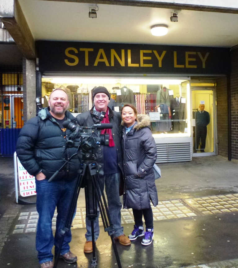 left to right: Jewish News One cameraman, Phil and Cindy outside the premises of Jewish tailors Stanley Ley in Middlesex Street, Petticoat Lane Market