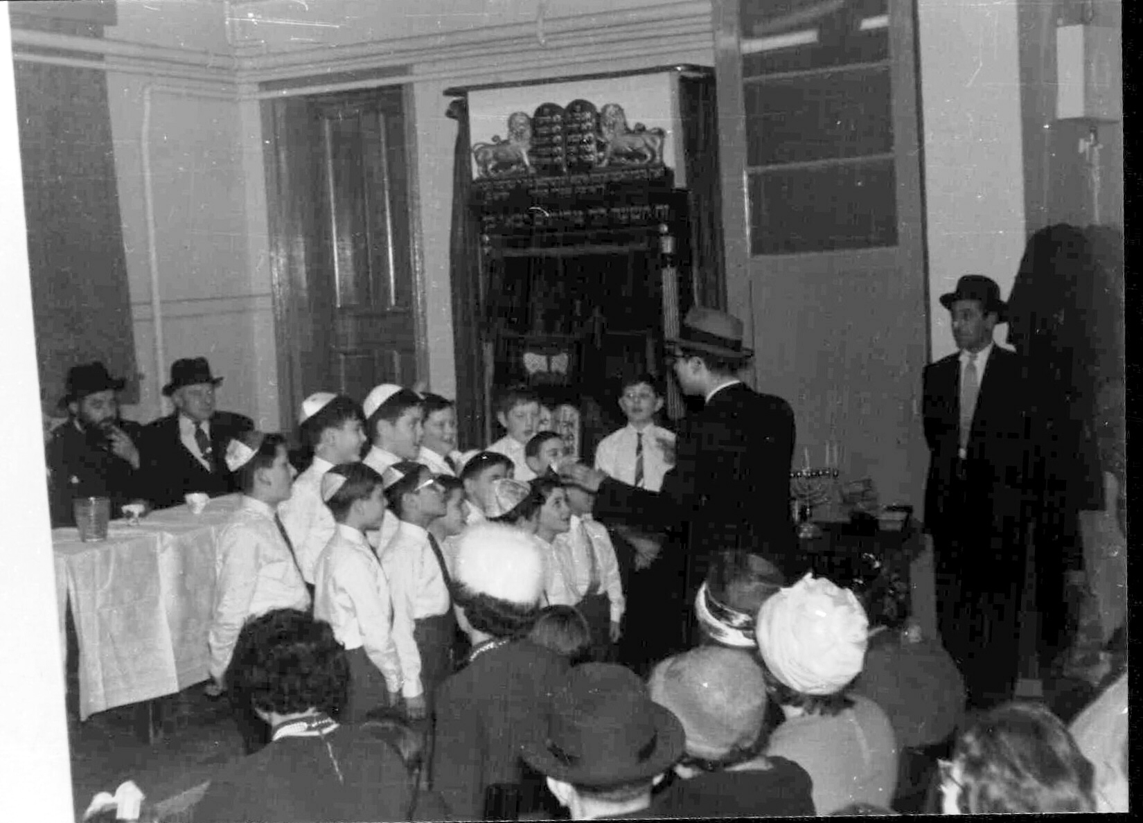 Rabbi S Halstuck of Commercial Road Great synagogue listening to the synagogue's boys choir, early 1950s